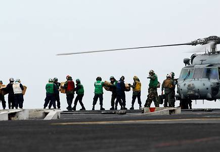 Sailors move food and water onto an HH-60H Sea Hawk assigned to the Black Knights of Anti- Submarine Squadron (HS) 4 on the flight deck of the aircraft carrier USS Ronald Reagan.