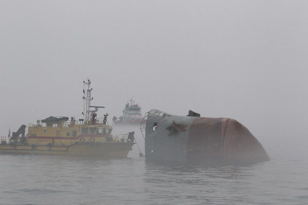 Rescuers travel in a boat as they search for survivors amidst heavy fog near a sunken barge, south of Hong Kong April 19, 2013. REUTERS/Apple Daily