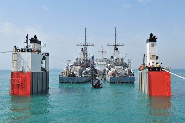 (Feb. 24, 2013) Mine countermeasure ships USS Pioneer (MCM 9) and USS Warrior (MCM 10) rest atop merchant vessel Super Servant III as it slowly rises to the surface during a heavy lift operation. U.S. Navy Photo.