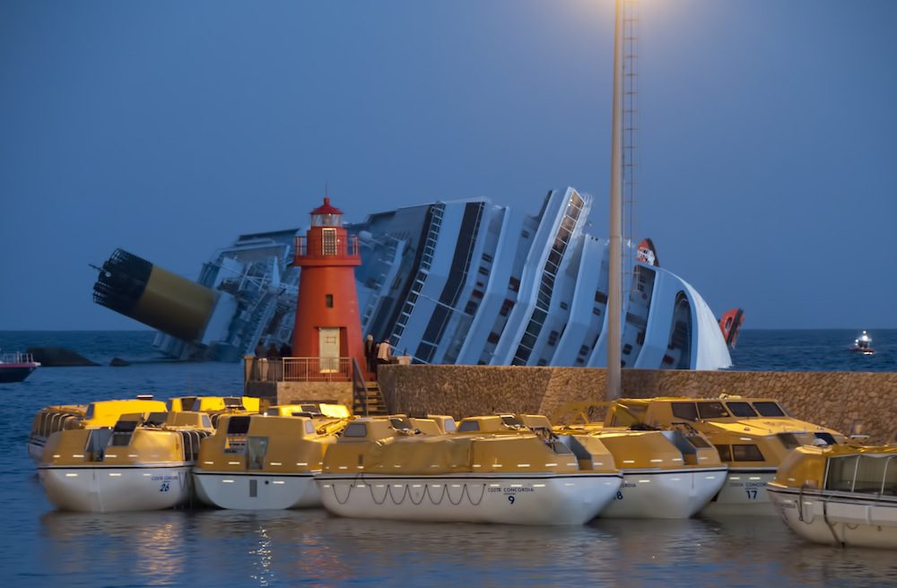 The Costa The lifeboats were moored inside the harbor pier before dawn. The grounded ship sank in background.