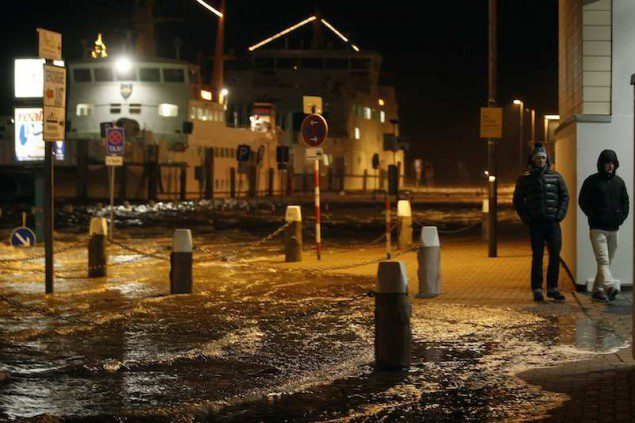People walk past a flooded street at the harbour in Norddeich, December 5, 2013. Hurricane-force Storm Xaver blasted towards mainland Europe on Thursday after cutting transport and power in northern Britain and killing three people in what meteorologists warned could be the worst storm to hit the continent in years.     REUTERS/Ina Fassbender